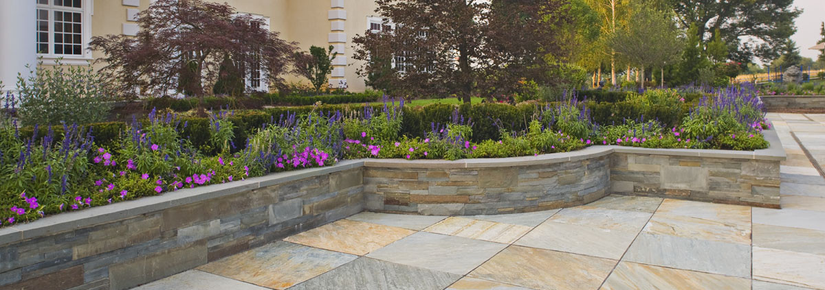 Landscape design: house, Norwegian buff and Pennyslvania bluestone patio bordered by dry-laid stone retaining walls & mixed borders Design: Cording Landscape Design Inc.